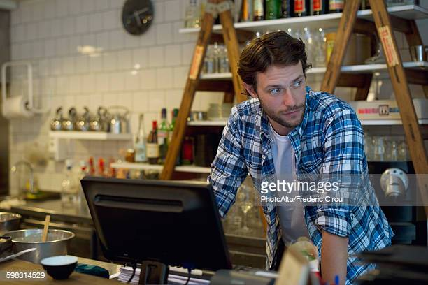 cafe owner standing behind cash register - register stock photos and pictures