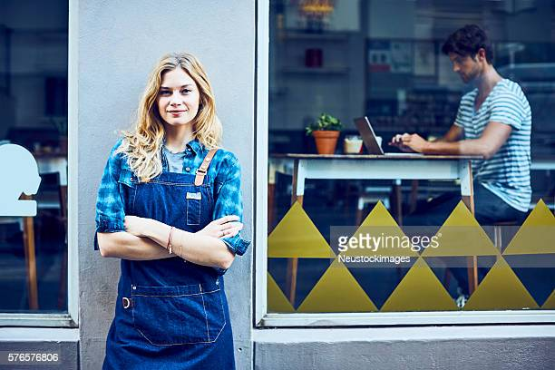 Cafe owner with arms crossed outside front