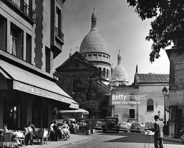 Cafe patrons watch an artist paint the cathedral of SacreCoeur in the Place Du Tertre Montmartre Paris circa 1950