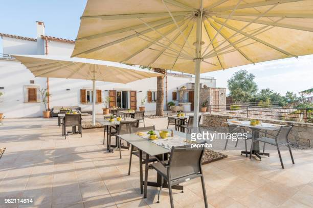 cafe tables from hotel under white umbrellas - patio stock pictures, royalty-free photos & images