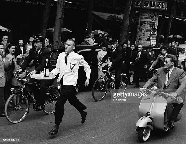 Cafe waiter Fribault carries a tray loaded with glasses and a bottle of Byrrh through the streets of Paris in a competition
