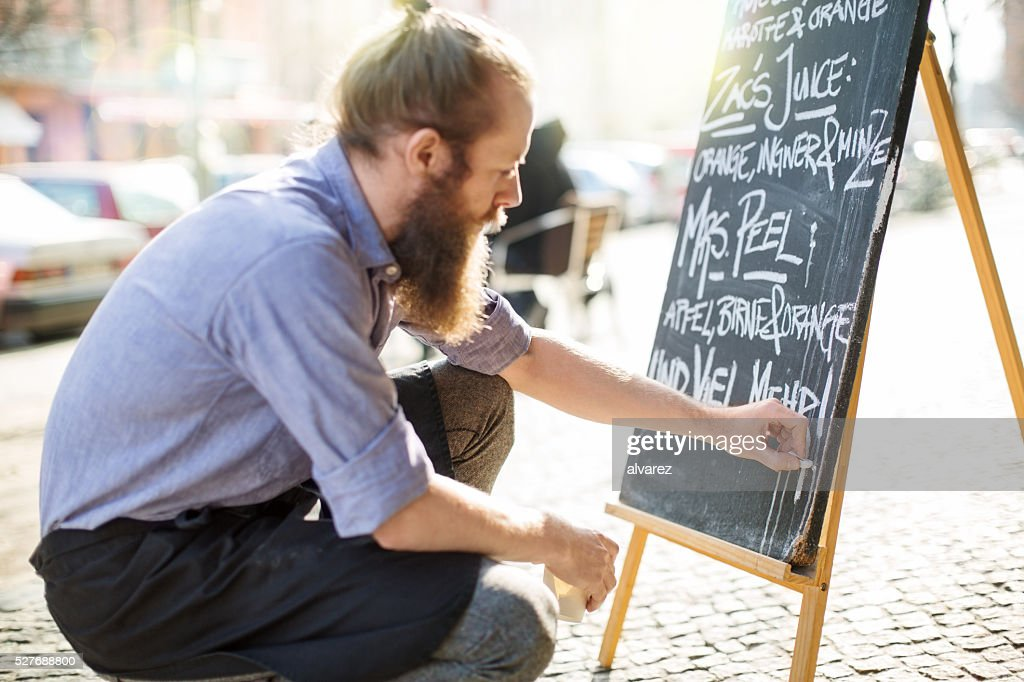 Cafe waiter writing todays special on the board : Stock Photo