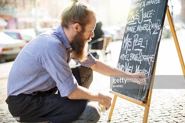 Cafe waiter writing todays special on the board