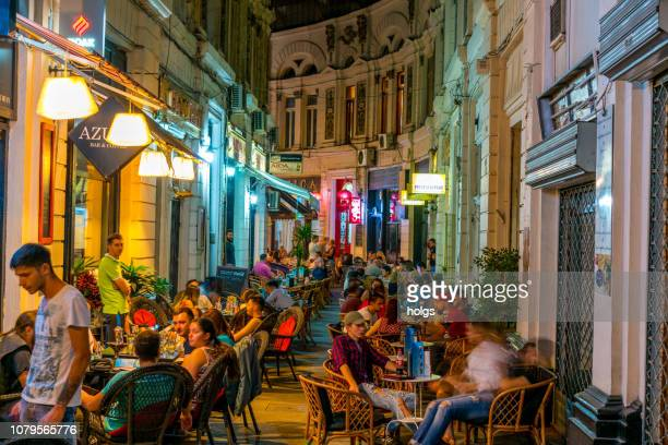 cafes within the pasajul macca- vilacrosse arcade at night in bucharest, romania, europe - bucharest stock pictures, royalty-free photos & images