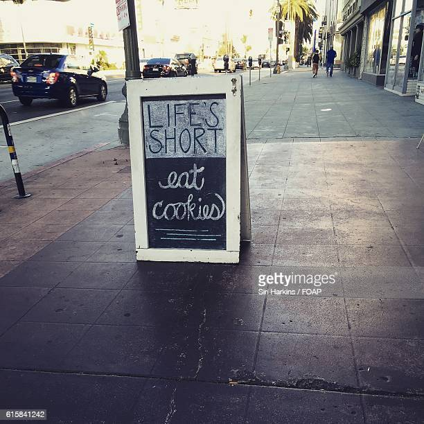 Cafe's wooden sign board on sidewalk