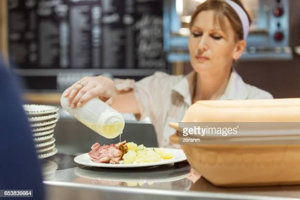 Cafeteria worker serving lunch