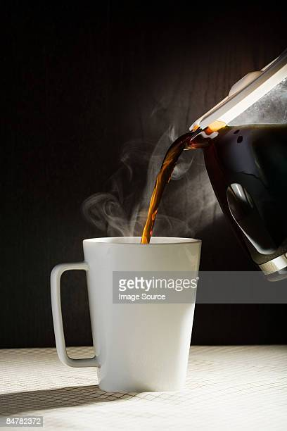 A cafetiere pouring coffee into cup