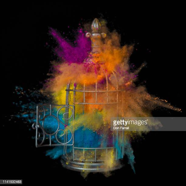 caged color breaking free - black background - don farrall stock pictures, royalty-free photos & images