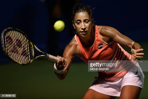 Cagla Buyukakcay of Turkey hits a return against Eugenie Bouchard of Canada during their quarter-final singles match at the BMW Malaysian Open...