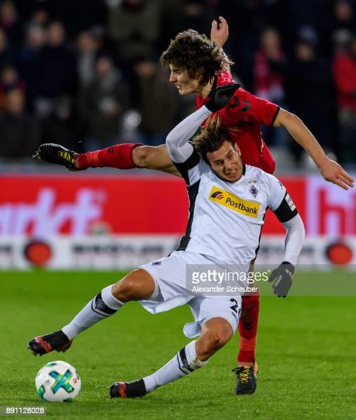 Caglar Soeyuencue of Freiburg challenges Raul Bobadilla of Moenchengladbach during the Bundesliga match between SportClub Freiburg and Borussia...