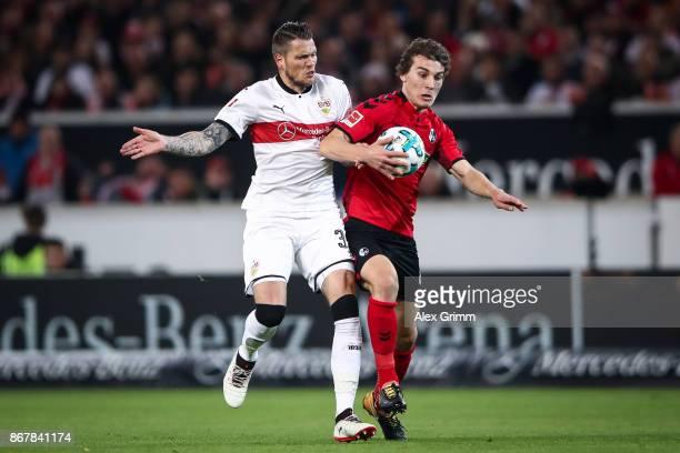 Caglar Soeyuencue of Freiburg during accidental handball as he battles for the ball with Daniel Ginczek of Stuttgart during the Bundesliga match...