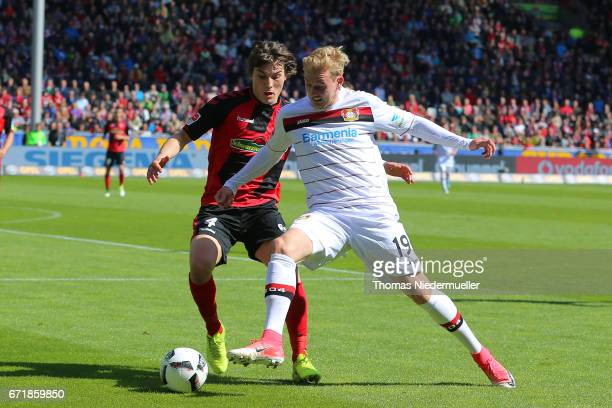 Caglar Soeyuencue of Freiburg fights for the ball with Julian Brandt of Leverkusen during the Bundesliga match between SC Freiburg and Bayer 04...