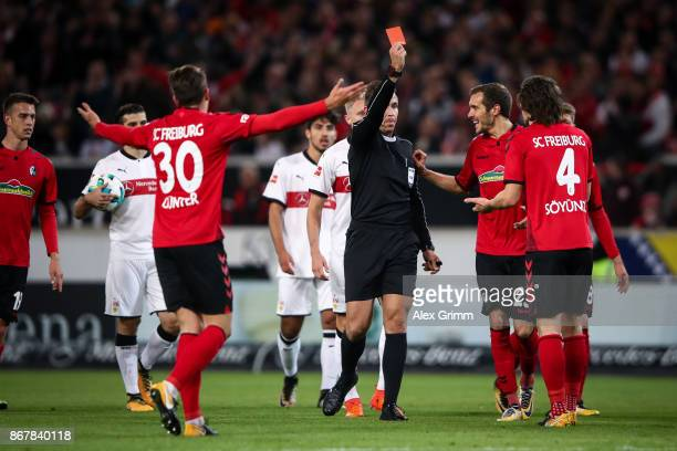 Caglar Soeyuencue of Freiburg is shown a red card by referee Tobias Stieler after accidental handball during the Bundesliga match between VfB...