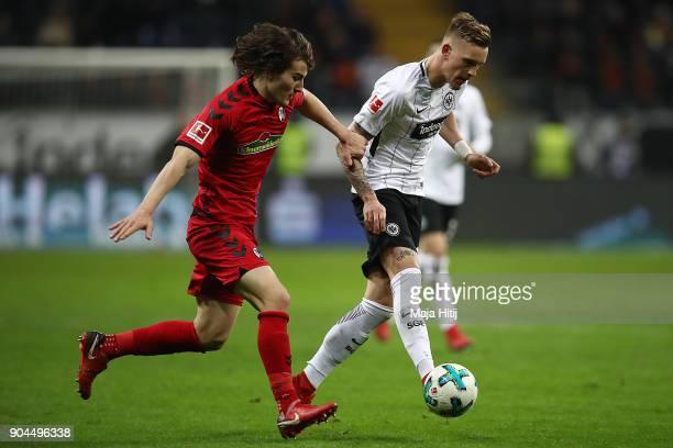 Caglar Soeyuencue of Freiburg runs with Marc Stendera of Frankfurt during the Bundesliga match between Eintracht Frankfurt and SportClub Freiburg at...