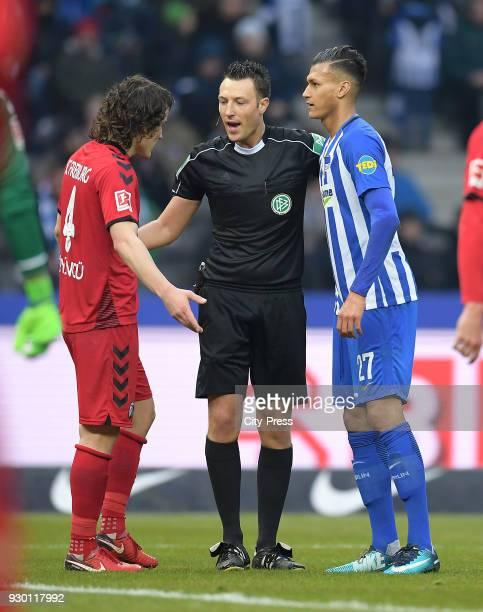 Caglar Soeyuencue of SC Freiburg referee Sven Jablonski and Davie Selke of Hertha BSC during the Bundesliga match between Hertha BSC and SC Freiburg...