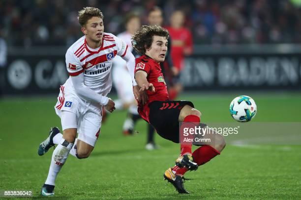 Caglar Souyuencue of Freiburg is challenged by JannFiete Arp of Hamburg during the Bundesliga match between SportClub Freiburg and Hamburger SV at...
