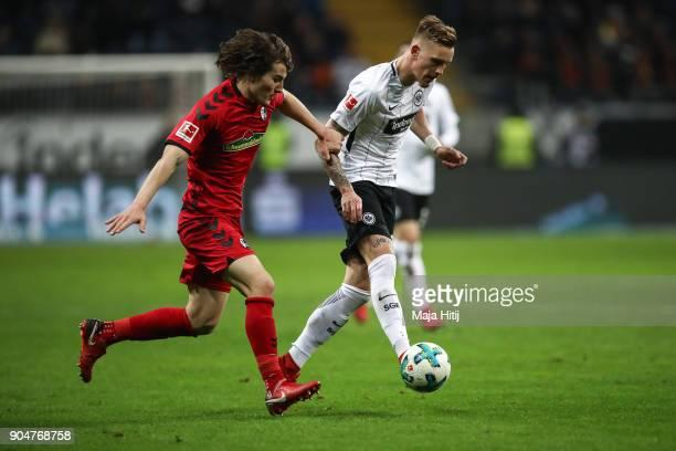 Caglar Soyuncu of SC Freiburg and Marc Stendera of Eintracht Frankfurt battle for the ball during the Bundesliga match between Eintracht Frankfurt...