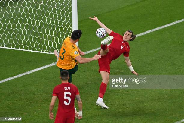 Caglar Soyuncu of Turkey attempts to clear the ball whilst under pressure from Kieffer Moore of Wales during the UEFA Euro 2020 Championship Group A...
