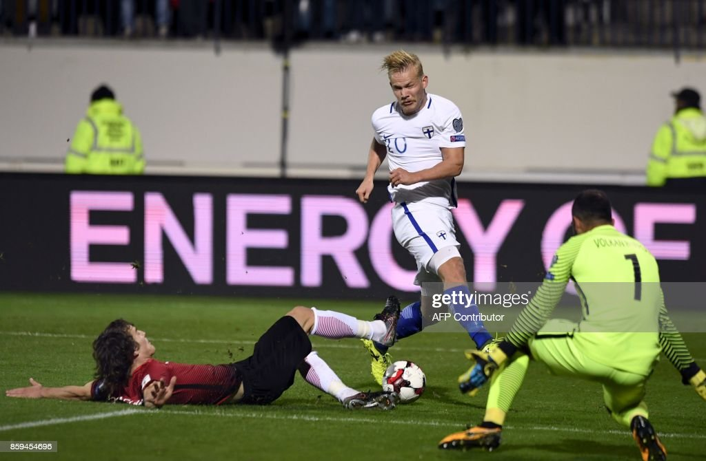 Caglar Soyuncu (L) of Turkey falls while Joel Pohjanpalo (C) of Finland shoots towards Turkey's goalkeeper Volkan Babacan (R) during the FIFA World Cup 2018 qualifying football match between Finland and Turkey in Turku, Southern Finland on October 9, 2017. / AFP PHOTO / Lehtikuva / Antti Aimo-Koivisto / Finland OUT