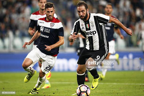Cagliari's defender Luca Bittante fights for the ball with Juventus' Argentinian forward Gonzalo Higuain during the Italian Serie A football match...