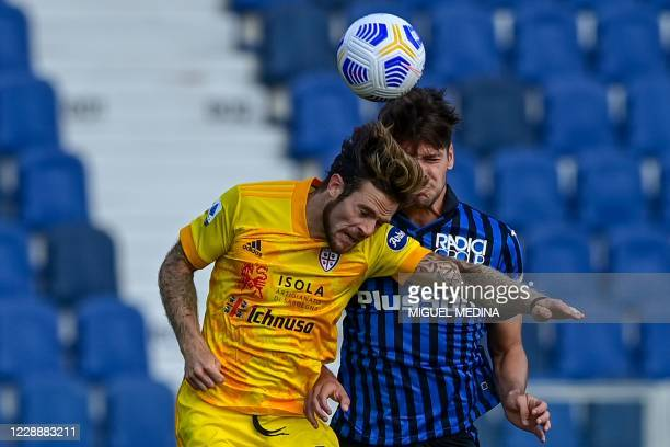 Cagliari's Uruguayan midfielder Nahitan Nandez and Atalanta's Albanian defender Berat Djimsiti go for a header during the Italian Serie A football...