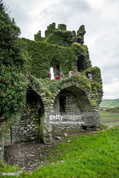 Cahersiveen, Kerry, Ireland. Ocotober 4, 2016. The old stone ruins of Ballycarberry Castle with people standing in areas of the second floor.