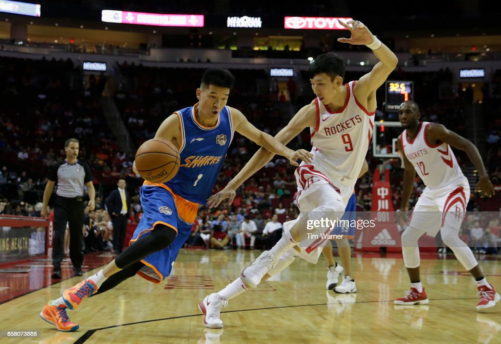 Cai Liang #1 of Shanghai Sharks drives the ball to the basket defended by Zhou Qi #9 of Houston Rockets in the second half at Toyota Center on October 5, 2017 in Houston, Texas.