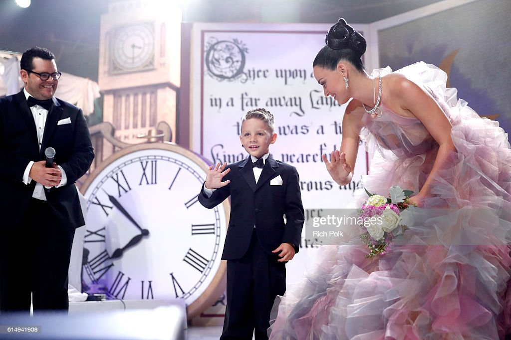Caiden Moran, CHLA Patient presents a bouquet of flowers to singer Katy Perry with Josh Gad onstage at 2016 Children's Hospital Los Angeles 'Once Upon a Time' Gala at The Event Deck at L.A. Live on October 15, 2016 in Los Angeles, California.