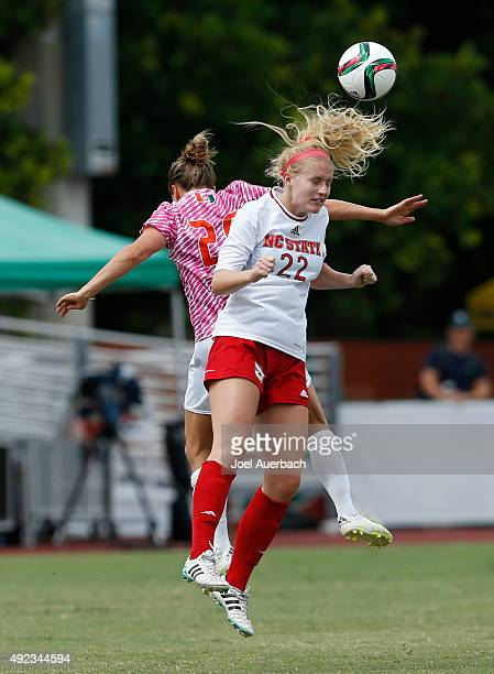 Cailyn Boch of the North Carolina State Wolfpack heads the ball away from Amy Schmidt of the Miami Hurricanes on October 11 2015 at Cobb Stadium in...
