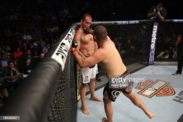 Cain Velasquez punches Junior Dos Santos in their UFC heavyweight championship bout at the Toyota Center on October 19 2013 in Houston Texas