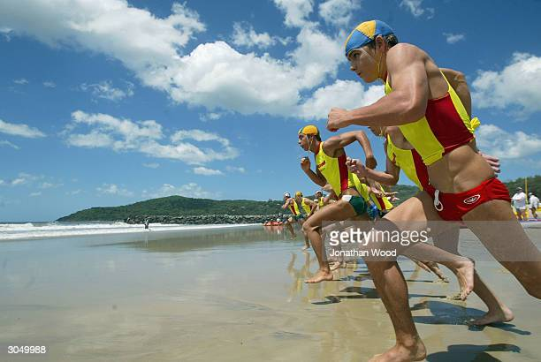 Caine Eckstein of Surfers Paradise heads for the surf in the Men's 19 years Ironman Event during day three of the Queensland Surf Lifesaving State...