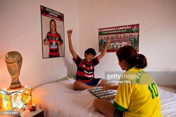 Caio de Mendonça and aunt Laura play 'Futebol do Botão' Button Football surrounded by football posters and memorabilia in their home in Rio de...