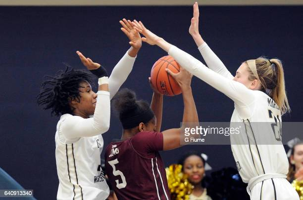 Caira Washington and Lexi Martins of the George Washington Colonials defend against G'mrice Davis of the Fordham Lady Rams at Charles E Smith...