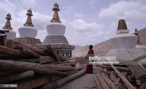 Cairen Wenci, a 19-year-old Tibetan monk, looks at the white pagodas, of which some were ruined last year at Jyegu Monastery in Jiegu, Yushu,...