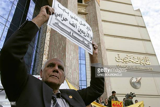 A supporter of Egypt's opposition proreform umbrella movement 'Kefaya' holds a sign calling for the demise of the government calling them 'Ali Baba...