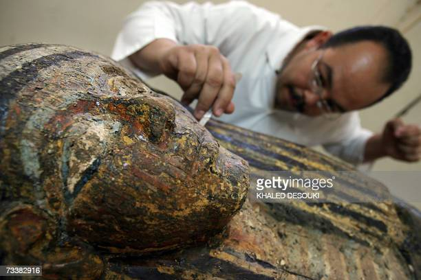 An Egyptian archaeologist works on a Sarcophagus which date back to a Pharoneic new Kingdom and were recently found near the famous Step Pyramid in...