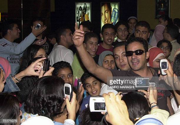 Egyptian actor Mohammed Ragab is surrounded by fans upon his arrival at a movie theatre in Cairo for the premiere of his new film 'Tumn Dastet...