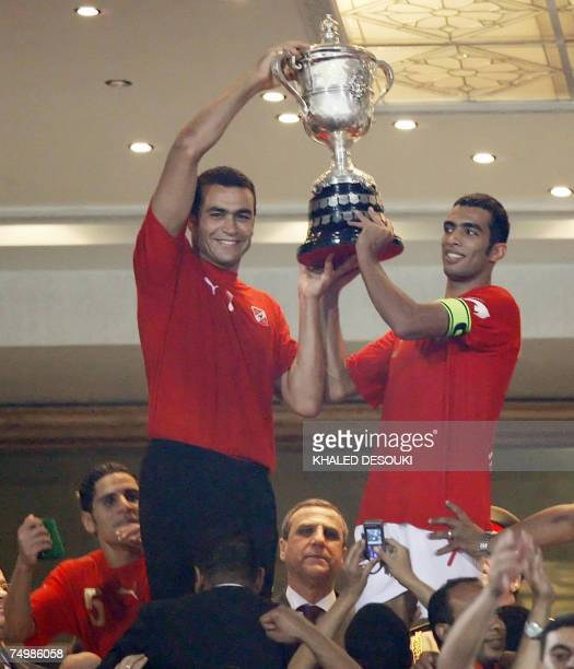 Egyptian captain of alAhly football team Shadi Mohamed and his teammate goalkeeper Issam elHadari hoist the cup after their victory vs Zamalek club...