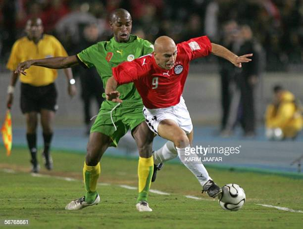 Egyptian forward Hossam Hassan , player in Masry , a legend in the national football at 40 years of age, trips as he runs away from Senegalese...