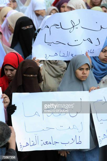 Egyptian students of Cairo University hold banners reading in Arabic 'It will never go down as long as we're alive' during a demonstration organized...