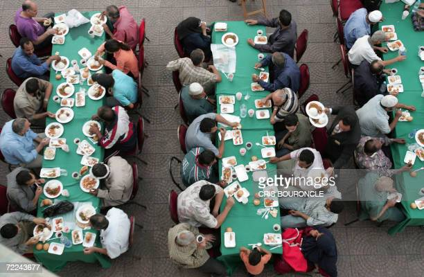 Needy Egyptians sitting at a makeshift dinning hall prepare to break their fast with Iftar a meal traditionally shared with family and friends while...