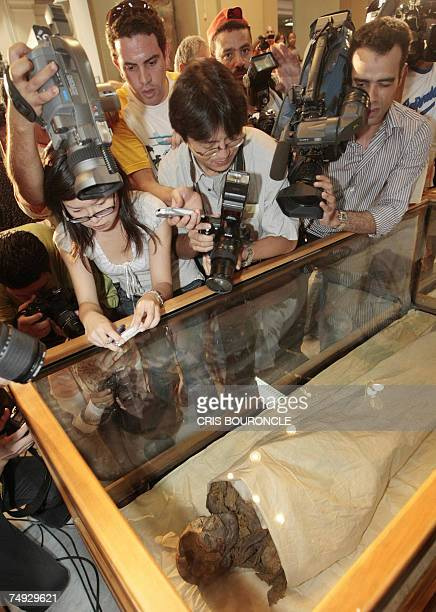 Photographers and general public crowd the sides of the glass case containing the mummified remains of Queen Hatshepsut ancient Egypts most famous...