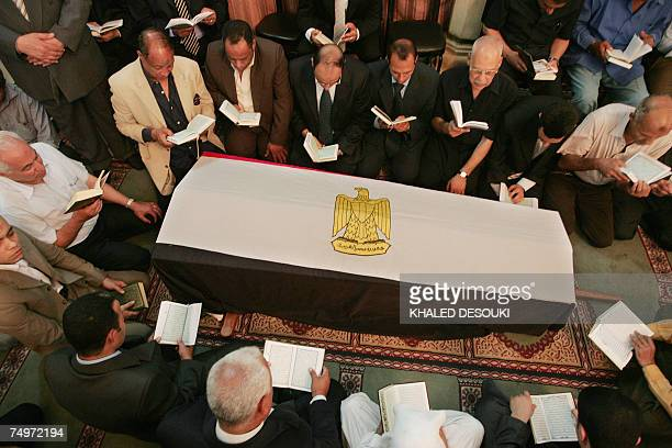 Relatives and friends of Egyptian billionaire Ashraf Marwan read the holy Koran around his coffin covered by the Egyptian flag during his funeral...