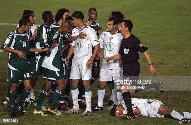 Tunisian referee Murad Daami tries to break up a fight between Libyan and Moroccan football players, during the knock-out round game between Libya...