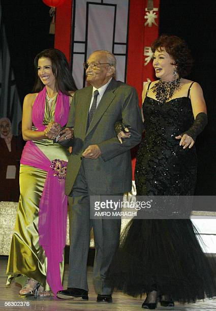 Veteran Egyptian actor Abdel Monem Madbuli arrives on stage with film stars Hanan Turk and Lebleba at the 29th edition of the Cairo international...