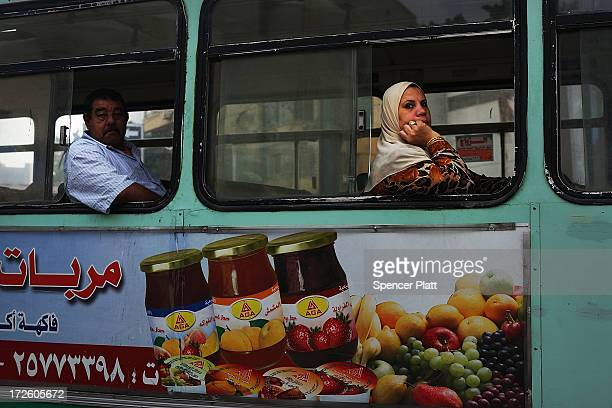 Cairo residents look out from a bus as the Egyptian military stands guard at a roadblock in the district of Giza the morning after the first...