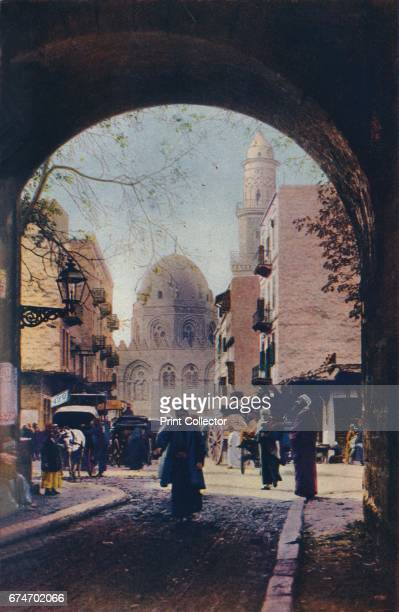 Cairo. Traffic is thick in the streets near the old Mahomedan University, the Mosque El Azhar, here framed in an archway', c1920. A depiction of...