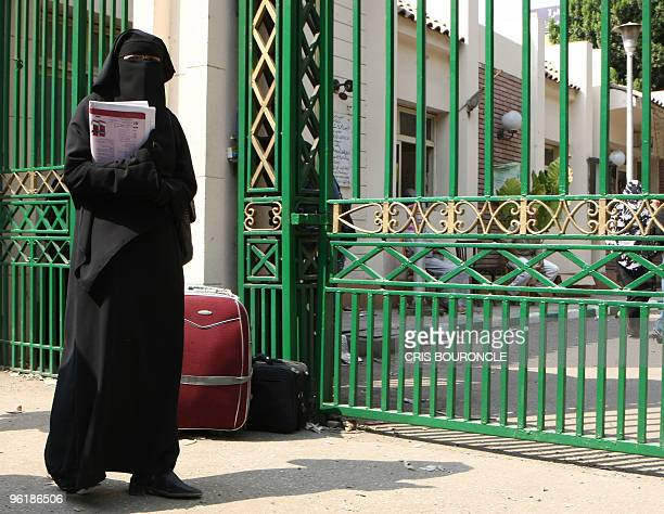 Cairo University student wearing a niqab, a black veil which covers the face except for the eyes, stands with her luggage outside the university...