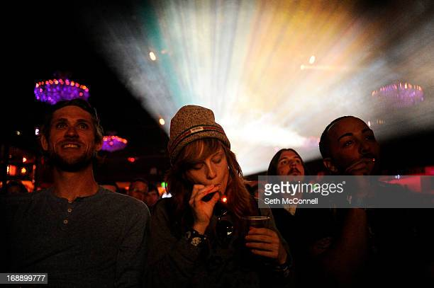 Caiti Beckwith of Denver Colorado smokes a joint while watching the Snoop Lion documentary Reincarnated during the first ever Green Carpet event as a...