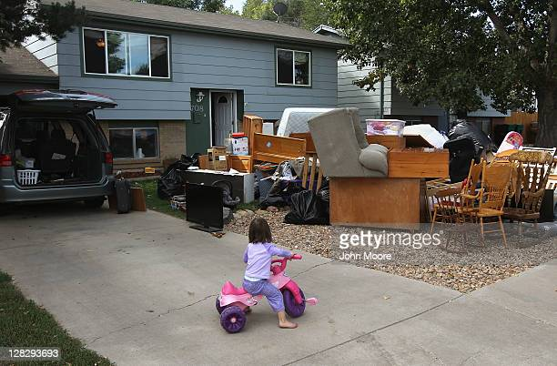 Caitlin Barbiere 2 1/2 plays in the driveway as her family's possessions sit piled in the front yard during a home foreclosure eviction on October 5...